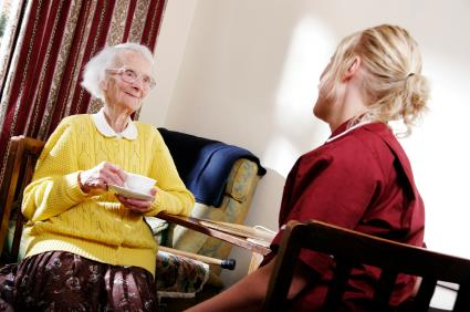 Care home senior elderly woman nurse cup tea smiling